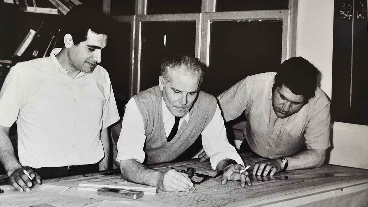 Theofanis Bekris and his Sons over a table with shipbuilding plans